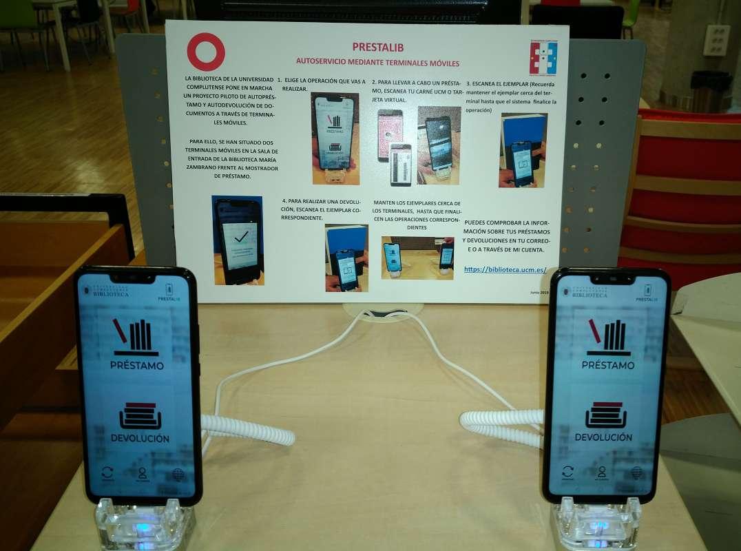 Dispositivos móviles y cartel con instrucciones del servicio Prestalib